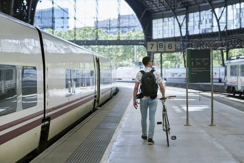 Man pushing bicycle through a station - JNDF00130