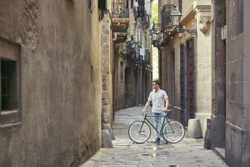 Man standing with his bicycle in a narrow alley - JNDF00142