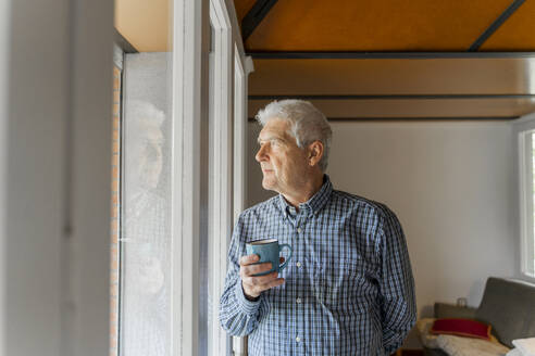 Serious senior man looking at home through window - AFVF04115