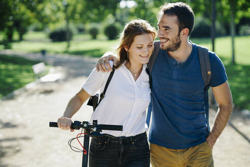 Happy couple with electric scooter in a city park - JSMF01323