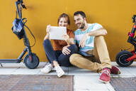Portrait of smiling couple with electric scooters using digital tablet - JSMF01341