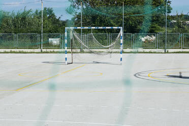 Croatia, Nin, Soccer goal standing in empty schoolyard - NGF00526