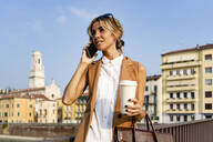 Smiling woman with coffee to go using smartphone in the city - GIOF07309