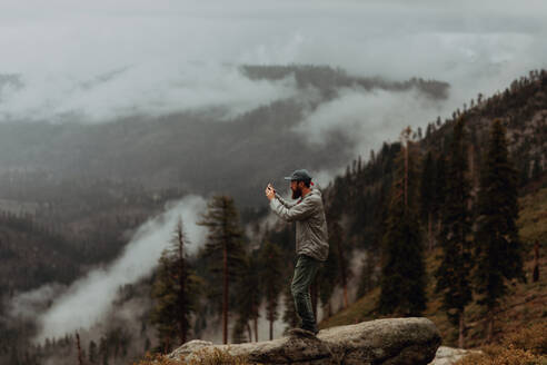 Hiker taking photograph of view of fog covering valley, Yosemite National Park, California, United States - ISF22316
