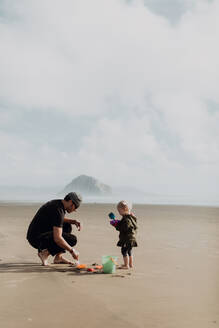 Father and toddler playing with sand on beach, Morro Bay, California, United States - ISF22334