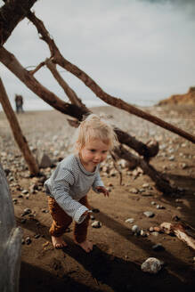Toddler playing beside wickiup on beach - ISF22346