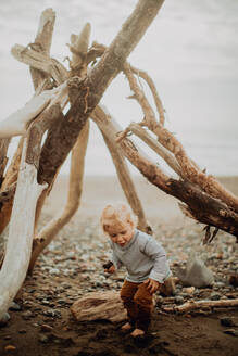 Toddler playing beside wickiup on beach - ISF22355
