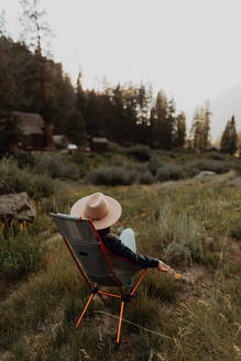 Young woman in stetson relaxing on deck chair in rural valley, rear view, Mineral King, California, USA - ISF22361
