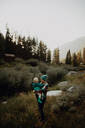 Mother carrying toddler daughter in rural valley, Mineral King, California, USA - ISF22367