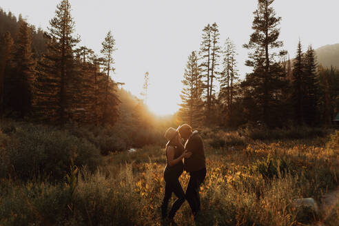 Pregnant mid adult couple face to face in rural valley at sunset, Mineral King, California, USA - ISF22376
