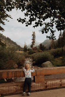Female toddler looking out at river from rural bridge, rear view, Mineral King, California, USA - ISF22379