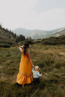 Mother holding toddler daughter's hand in rural valley, rear view, Mineral King, California, USA - ISF22391