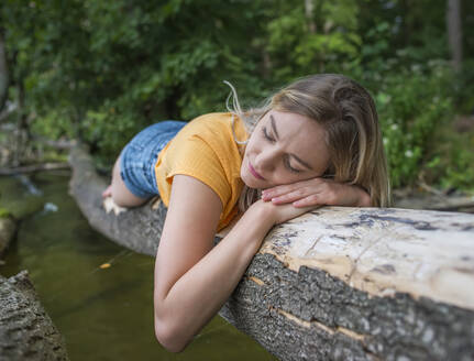 Woman laying on a tree trunk at lakeshore - BFRF02109