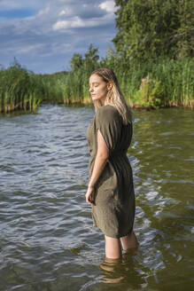 Woman with closed eyes standing in a lake - BFRF02130