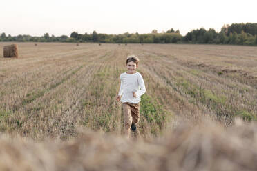 Smiling boy running over a stubble field - EYAF00625