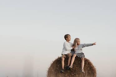 Two kids sitting on the haystack - EYAF00628
