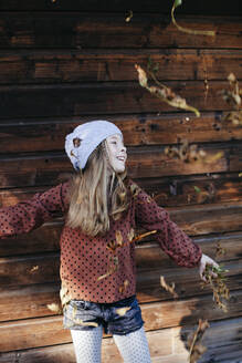 Smiling girl standing in front of a wooden wall outdoors - HMEF00654