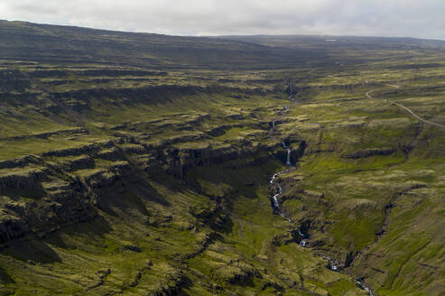 Öxi pass is a mountain pass at an elevation of 539m above the sea level, located in eastern Iceland. Pictured here is one fjords in this valley, standing approximately 600m high, with a beautiful waterfall running through it. - AAEF04577