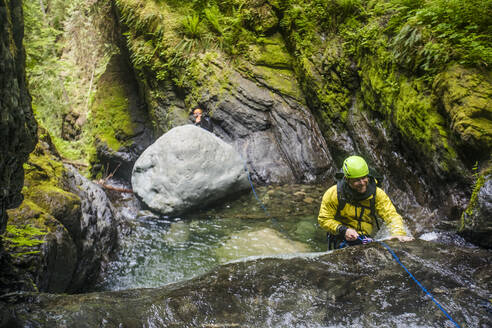 Man smiles while rappelling over the edge of a waterfall. - CAVF65789