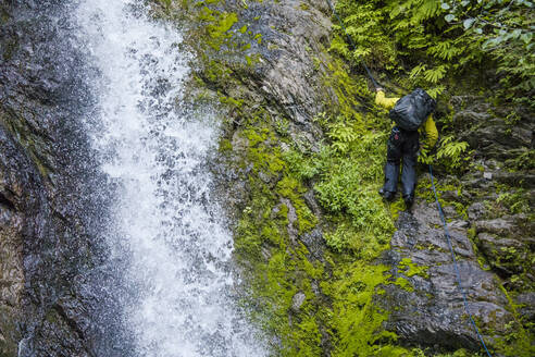 Backpacker rappels next to a rushing waterfall. - CAVF65804