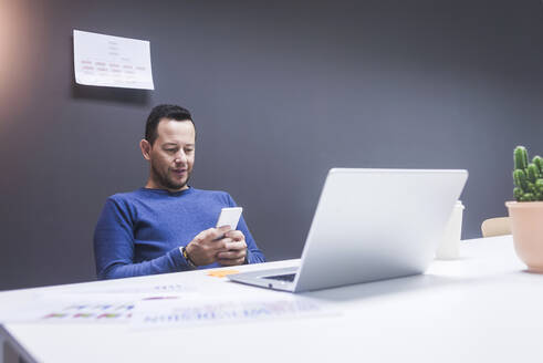 Young businessman reading his smartphone. Portrait of business man reading message with smartphone in office. Man working at his desk at office. - CAVF65855