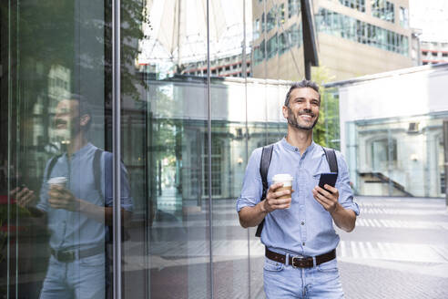 Smiling businessman holding cup of coffee and smartphone in the city, Berlin, Germany - WPEF02068