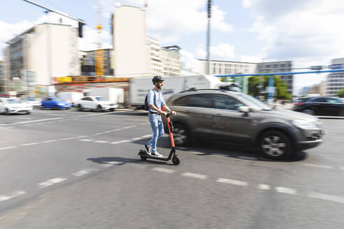 Businessman riding e-scooter on the street in the city, Berlin, Germany - WPEF02080