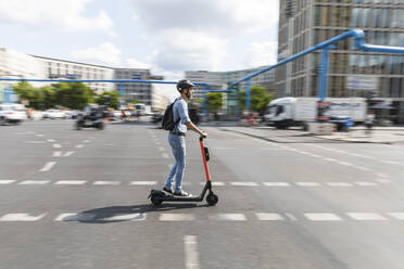 Businessman riding e-scooter on the street in the city, Berlin, Germany - WPEF02083