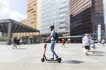 Businessman riding e-scooter on the pavement in the city, Berlin, Germany - WPEF02086
