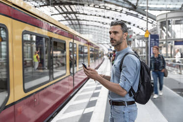 Businessman with smartphone at the station while train coming in - WPEF02095