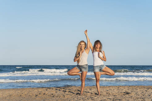 Two women praticing Acro Yoga on the beach - DLTSF00263