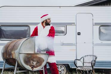 Santa claus preparing a barbecue in front of a camper - DAMF00196
