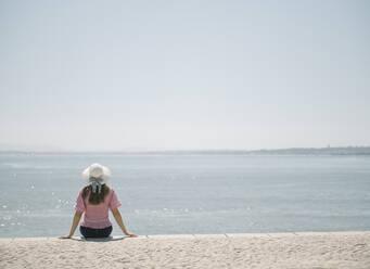 Rear view of woman sitting at the coast, Lisbon, Portugal - AHSF01001