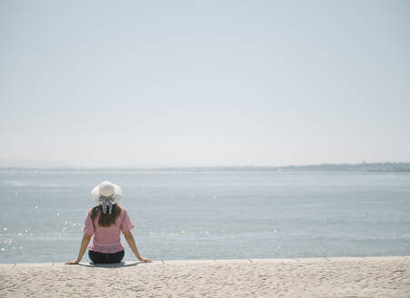 Rear view of woman sitting at the coast, Lisbon, Portugal - AHSF01001