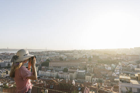 Woman taking a picture of the city panorama, Lisbon, Portugal - AHSF01004