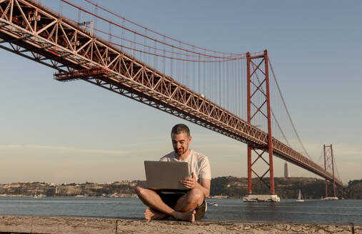 Man using laptop at 25th of April Bridge in Lisbon, Portugal - AHSF01013