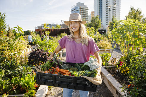 Portrait happy, confident young woman carrying fresh harvested vegetables in sunny, urban community garden - HEROF39445