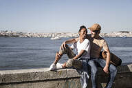 Happy young couple sitting on a wall at the waterfront, Lisbon, Portugal - UUF19062