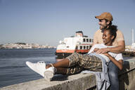 Happy young couple relaxing on a wall at the waterfront, Lisbon, Portugal - UUF19065
