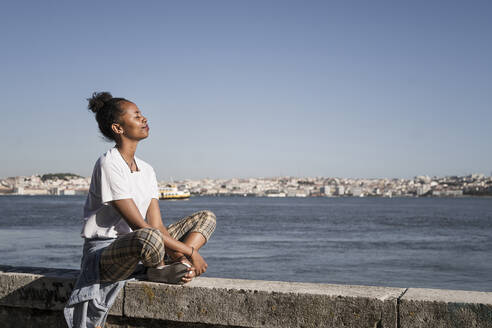 Young woman sitting on a wall at the waterfront with closed eyes, Lisbon, Portugal - UUF19068