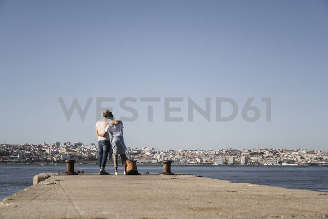 Young couple standing on pier at the waterfront, Lisbon, Portugal - UUF19086 - Uwe Umstätter/Westend61