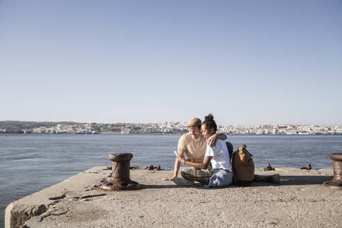 Young couple sitting on pier at the waterfront using cell phone, Lisbon, Portugal - UUF19092