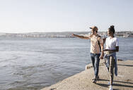 Young couple walking on pier at the waterfront, Lisbon, Portugal - UUF19098