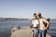 Happy young couple using cell phone on pier at the waterfront, Lisbon, Portugal - UUF19104