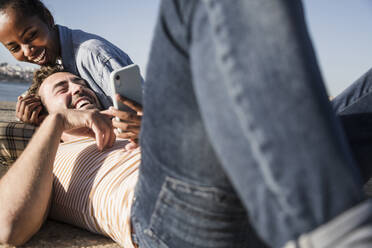 Happy young couple lying on pier using cell phone - UUF19110
