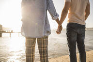 Close-up of couple holding hands at the waterfront at sunset - UUF19125