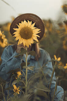Young woman behind a sunflower - OCAF00430
