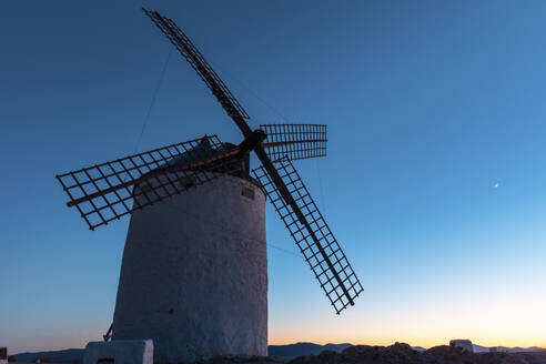 Spain, Province of Toledo, Consuegra, Old windmill standing against sky at dusk - WPEF02110