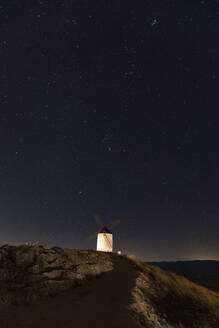 Spain, Province of Toledo, Consuegra, Starry sky over old windmill standing on top of hill at night - WPEF02113