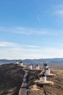 Spain, Province of Toledo, Consuegra, Country road along row of old windmills standing on top of hill - WPEF02131